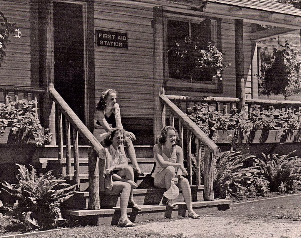 Three women sit on the steps of the first aid cabin