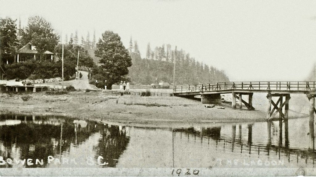 A wooden bridge crosses the lagoon where the causeway stands today, and at the end of it a wooden building.