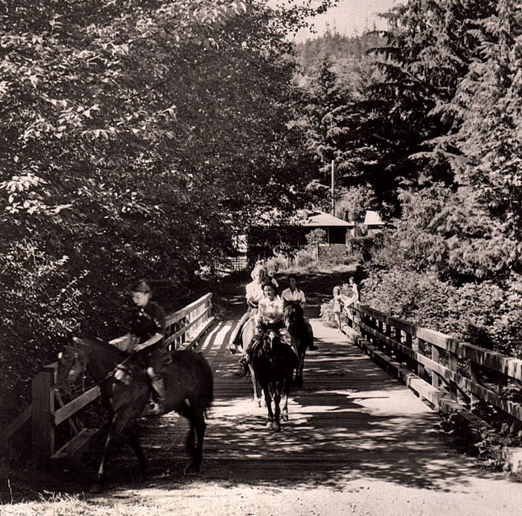 Women ride horses over a wooden bridge hemmed in on both sides by trees and shrubs