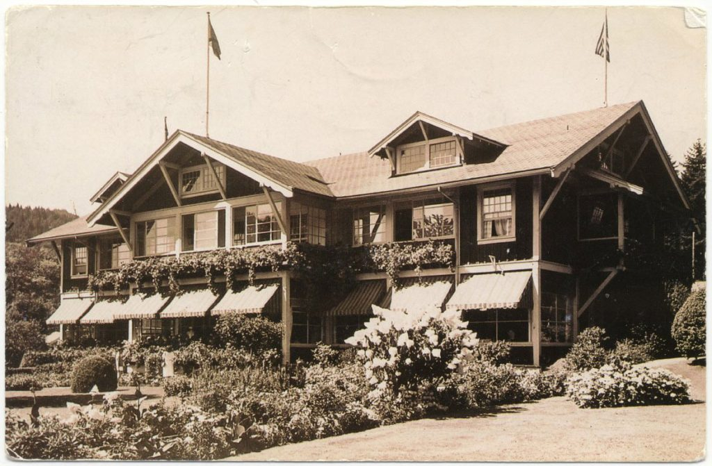A stately wooden hotel with striped canvas awnings and a flower garden in front.